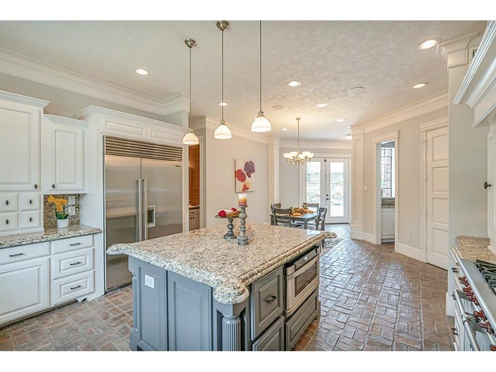 """BEFORE - The kitchen island and some weird corner """"wings"""" and lots of spotty granite."""