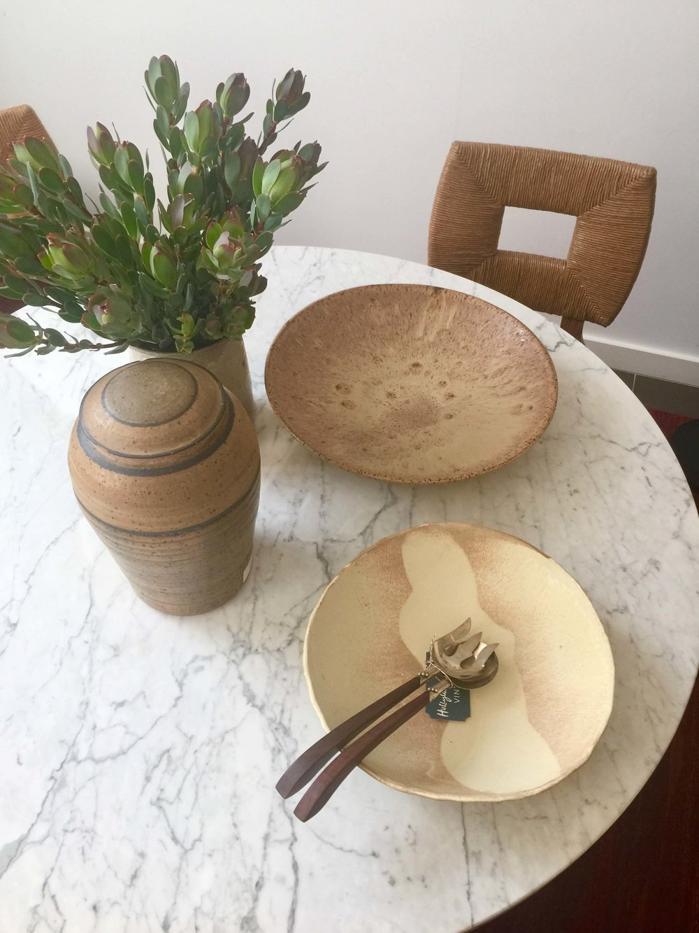 White marble table top with handmade ceramic bowls and rush chair in Hollywood at Home, Los Angeles home furnishings shop #whitemarble #marbletable #tablestyling