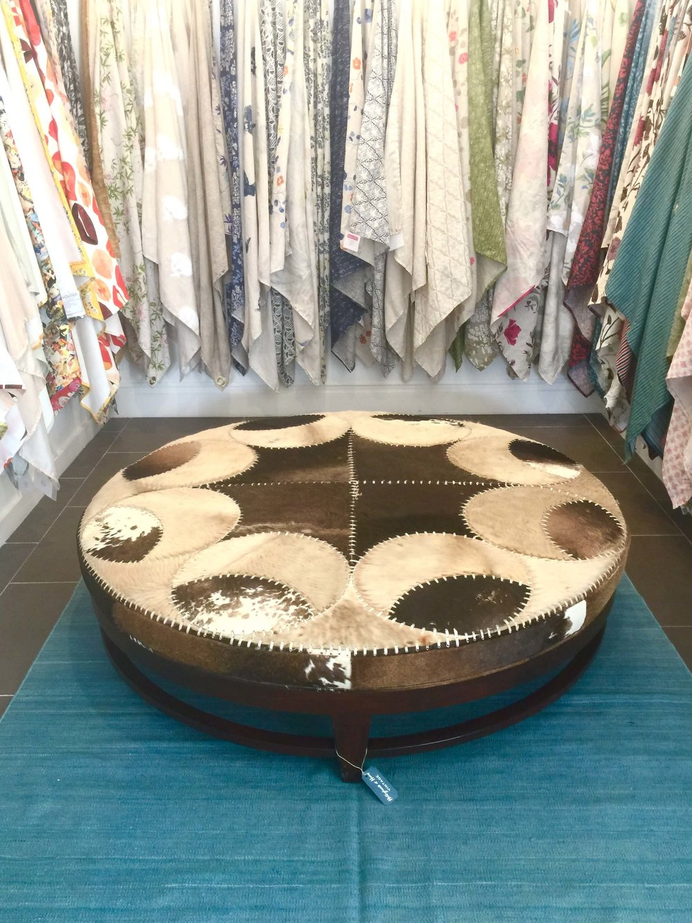 This creatively upholstered cowhide ottoman is surrounded by fabric samples at Hollywood at Home, Los Angeles home furnishings shop #cowhideottoman #homedecoratingideas