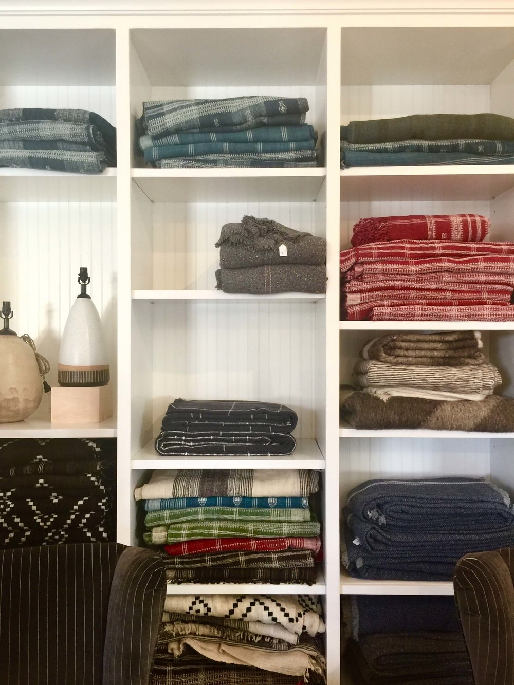 Blankets and throws in colorful textiles are stacked in open shelving in Hollywood At Home, Los Angeles home furnishings shop #blankets