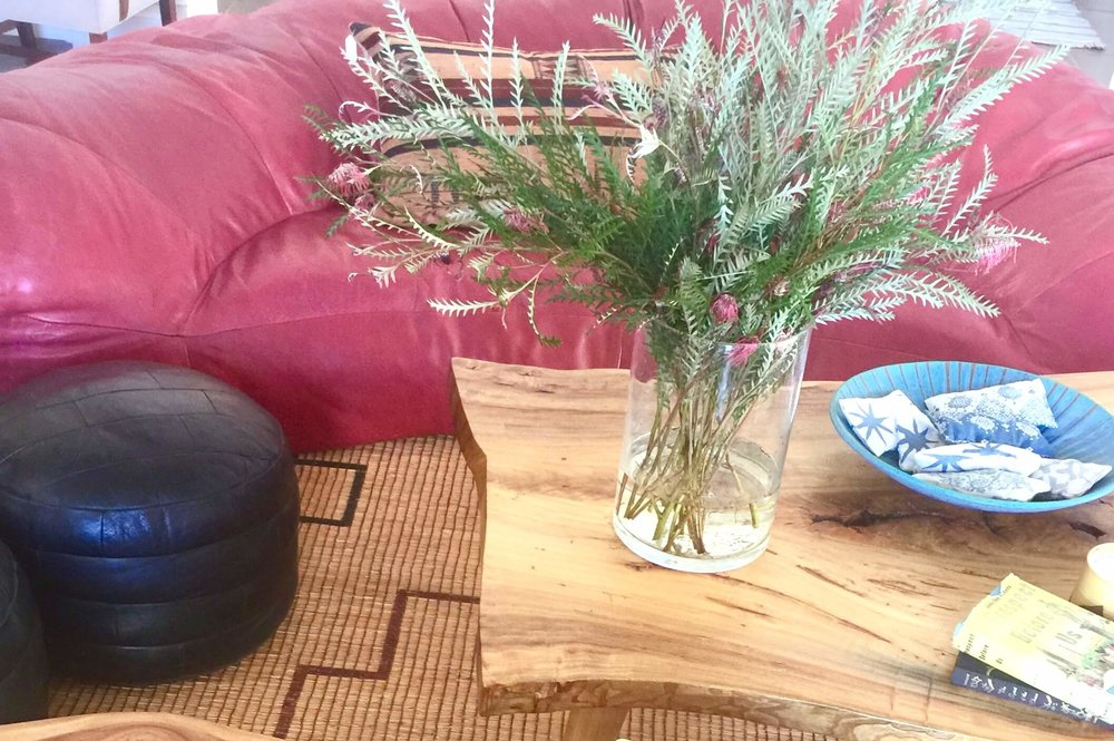 Live edge coffee table and red leather sofa in Hollywood at Home in Los Angeles #liveedge #leathersofa #vintagerug #decoratingideas