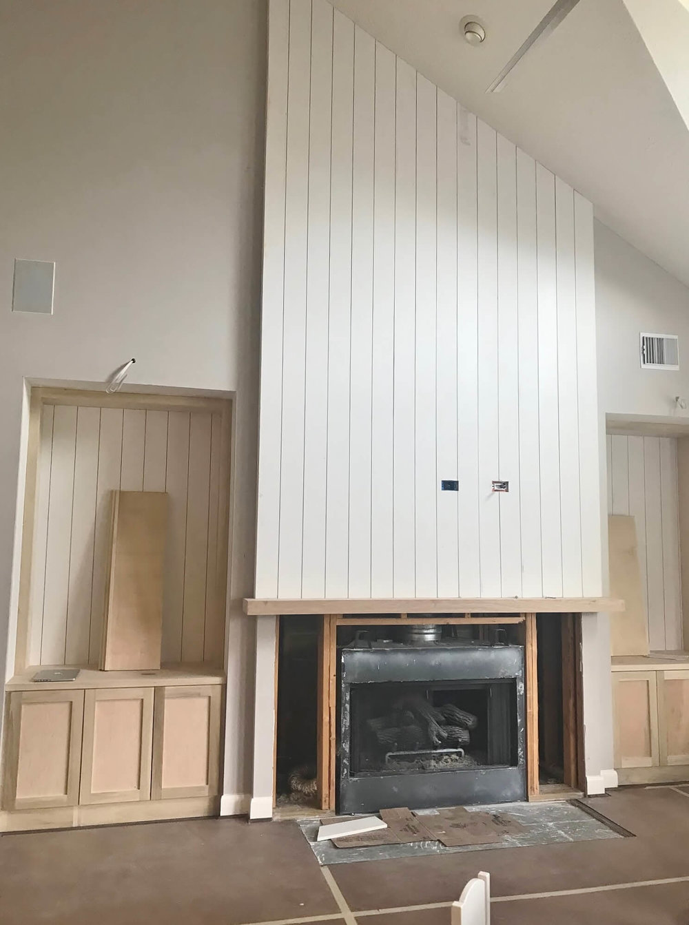 IN PROGRESS - This new fireplace wall has vertical paneling and symmetrical built-ins on each side for a cleaner look. We'll have two library arm type light fixtures above the built-ins to illuminate the open shelving on each side. #shiplap #fireplaceremodel