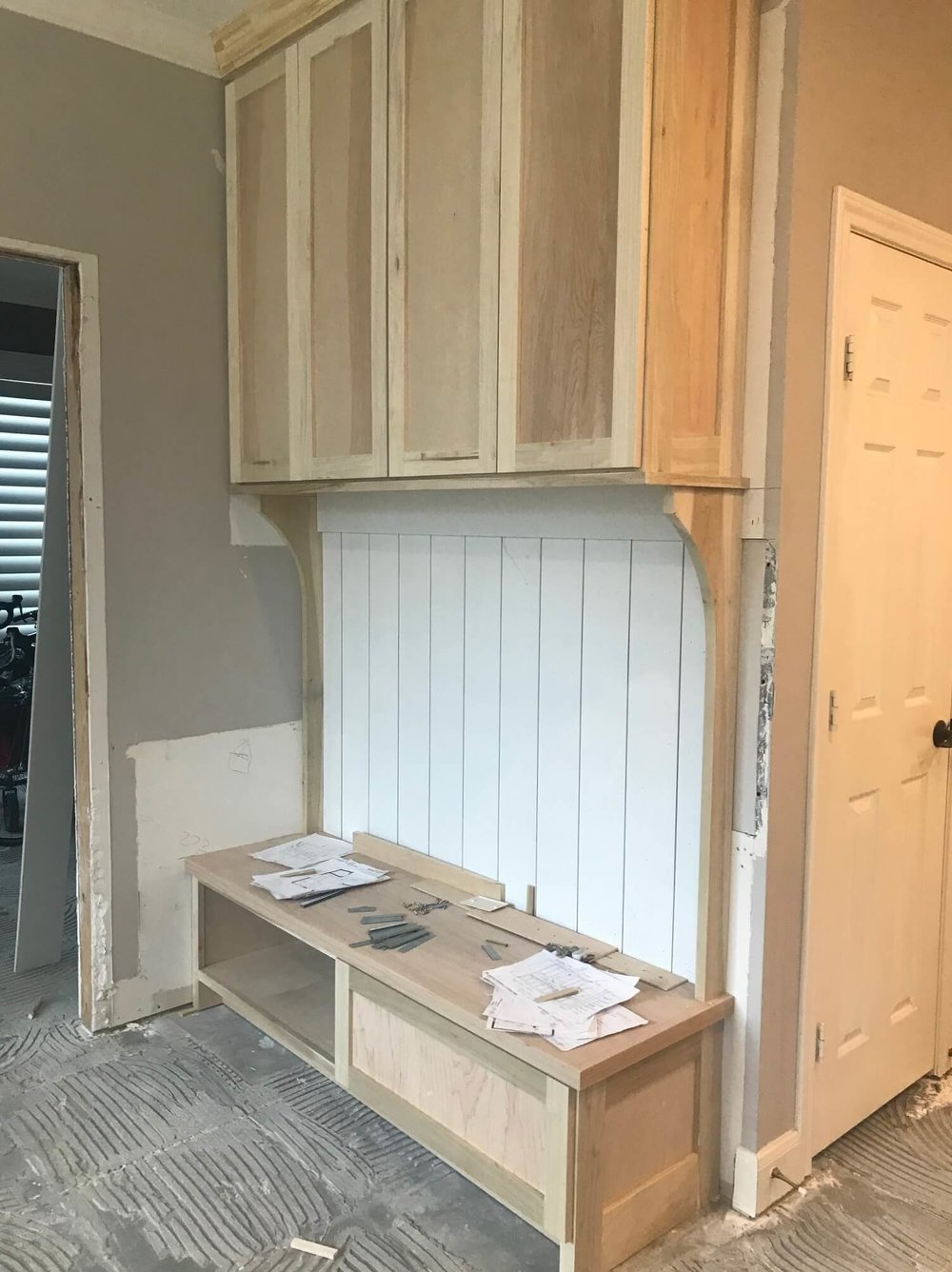 IN PROGRESS - This bench with storage above will be much more useful for this family. The paneling detail from the fireplace wall is repeated here. #shiplap #mudroom