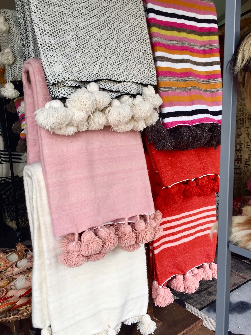 Moroccan blankets with pom poms in bright colors seen at Round Top, TX at Arbor Antiques #moroccan #pompom #blanket #roundtop