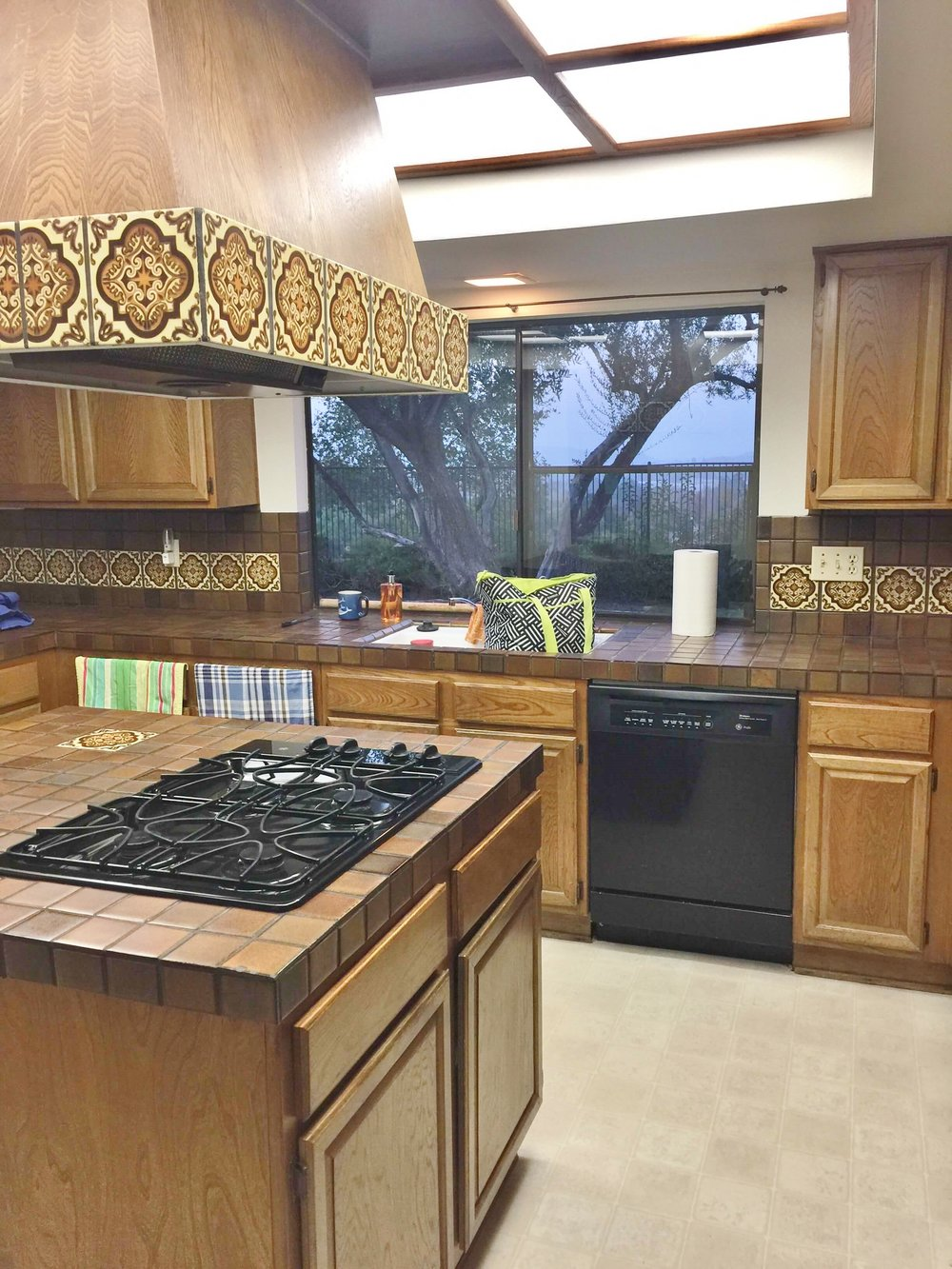 kitchen window and hood with brown wood cabinets