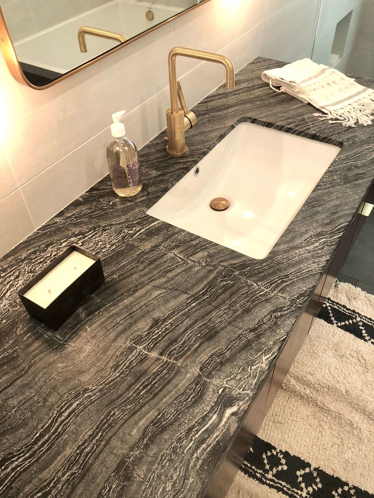 Contemporary bathroom style with natural stone counter and brushed brass fixtures | Assembledge+ Architects, Dwell on Design, Los Angeles, California #bathroomdesign #bathroomdesignideas