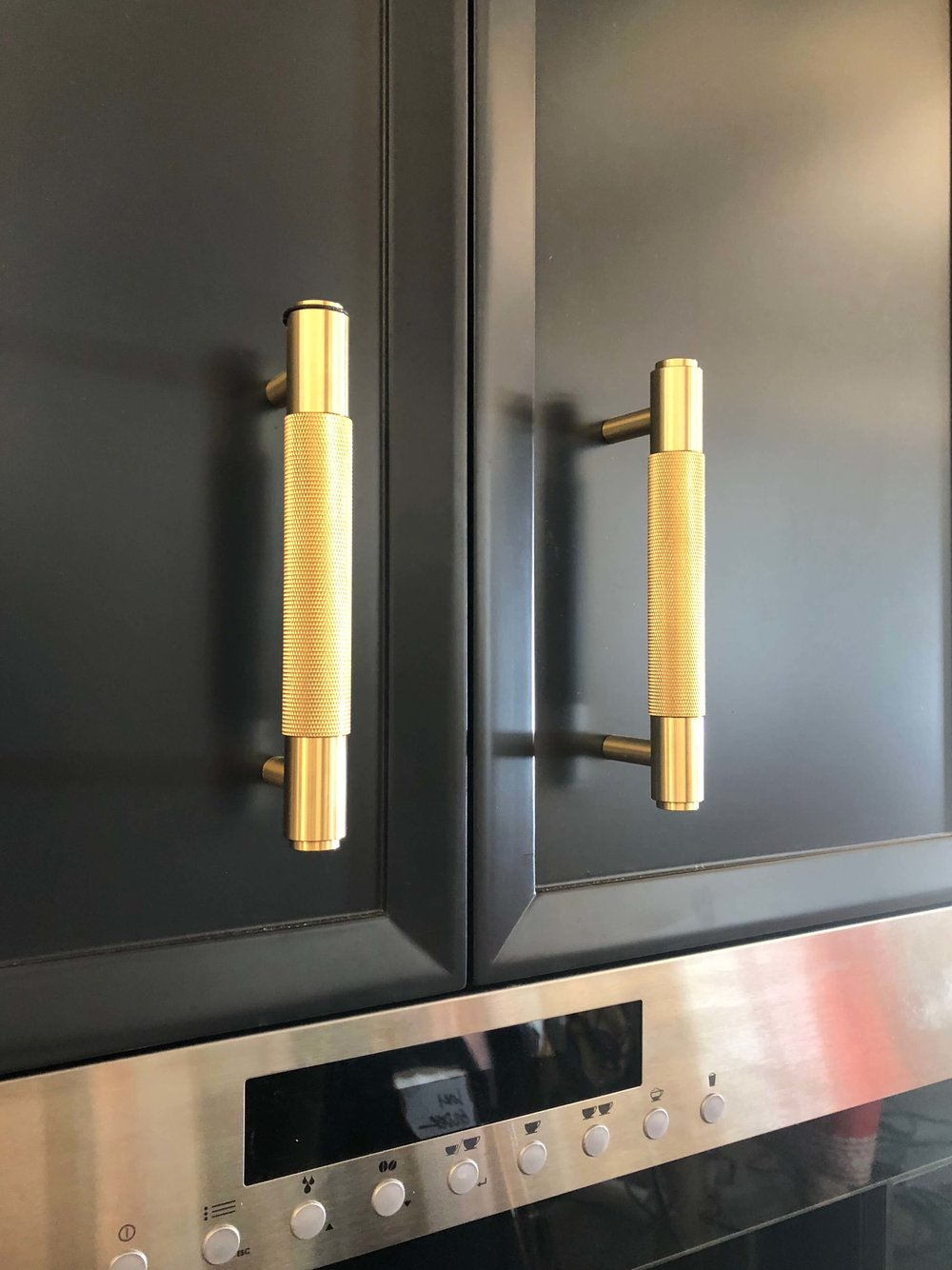 Brass cabinet pulls on black cabinets -  Kitchen designed by Jeanne K Chung