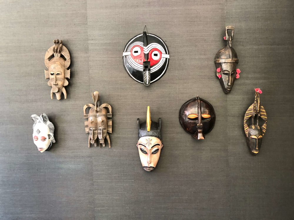 Global style in the Traveler's Room with masks on grasscloth walls, Designer: Parker West Interiors, Pasadena Showcase House of Design #masks #globalstyle #grasscloth
