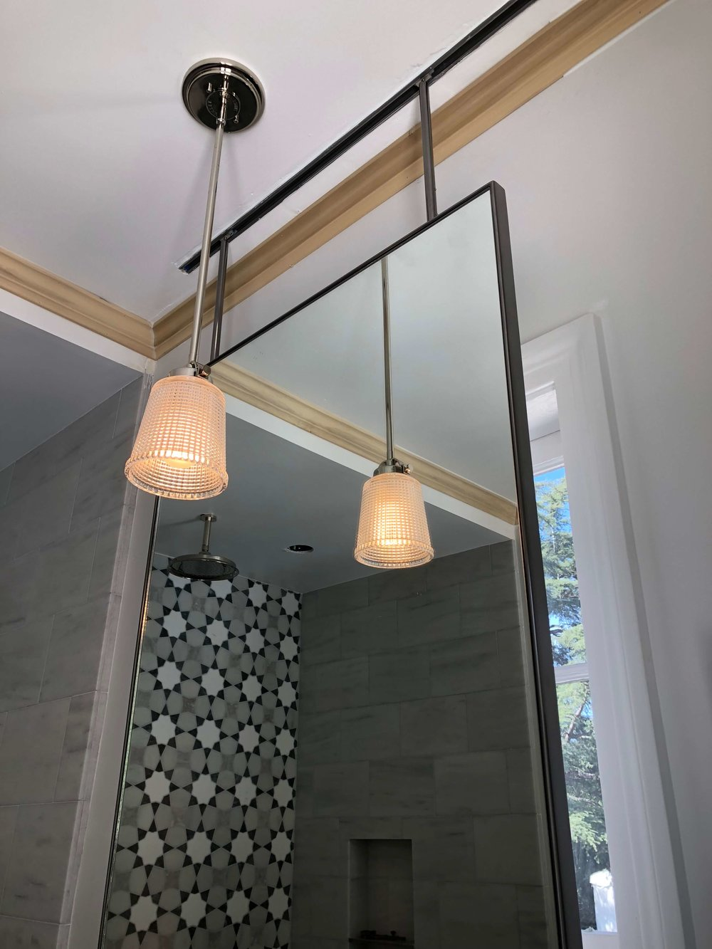 Bathroom mirror  hung over window with pendant lighting and mosaic tile in shower - Designer: Parker West Interiors, Pasadena Showcase House