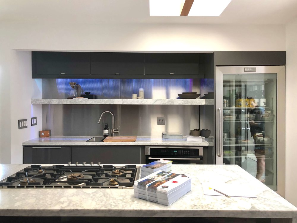Modern kitchen with stainless steel backsplash and glass front refrigerator #kitchendesign #contemporarykitchen