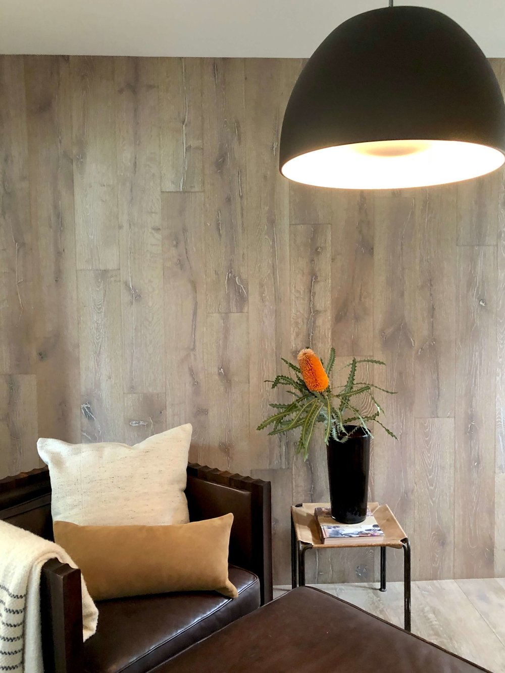 Lounge seating area with wood plank wall #woodwall #leatherchair