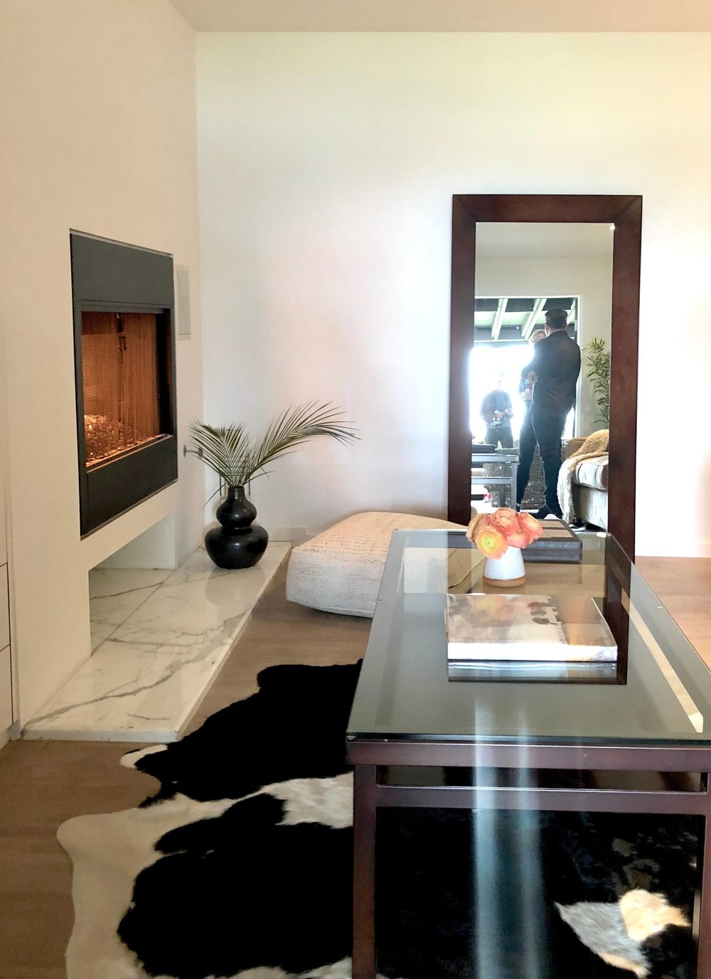 Lower den with leaning mirror, fireplace and cowhide rug #cowhiderug #leaningmirror