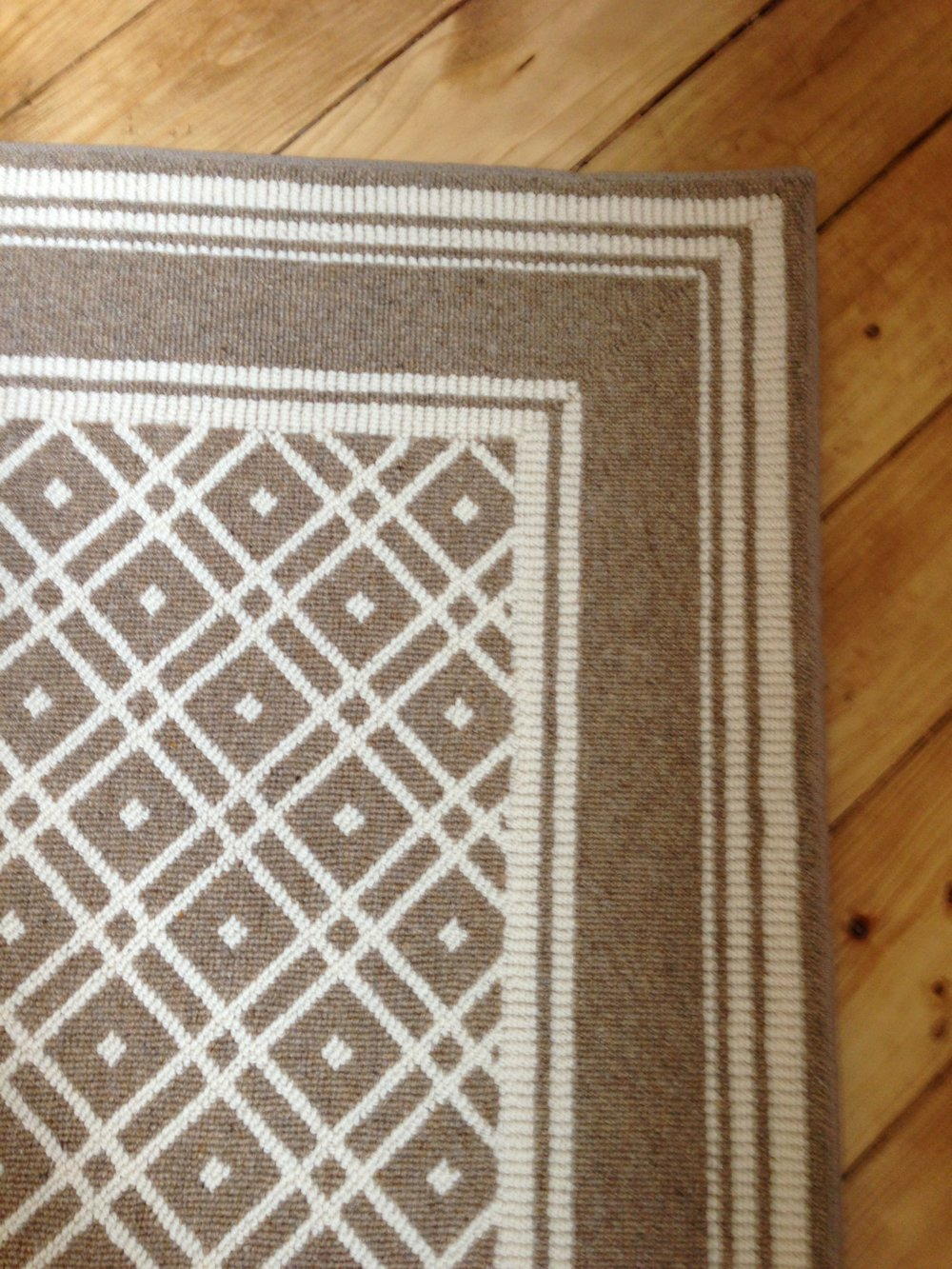 Custom beige and white wool rug with border on pine floors - Americana style gameroom, Carla Aston, Designer