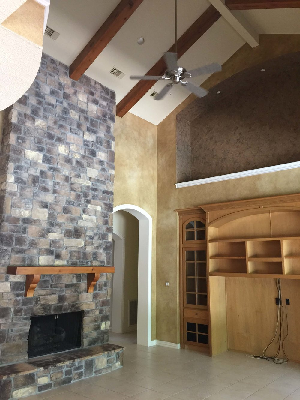 BEFORE - Family room with tall, dark fireplace and giant niche