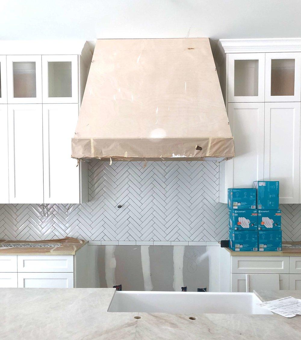 Kitchen remodel in progress - Herringbone backsplash is in, hood is being prepared for special finish.