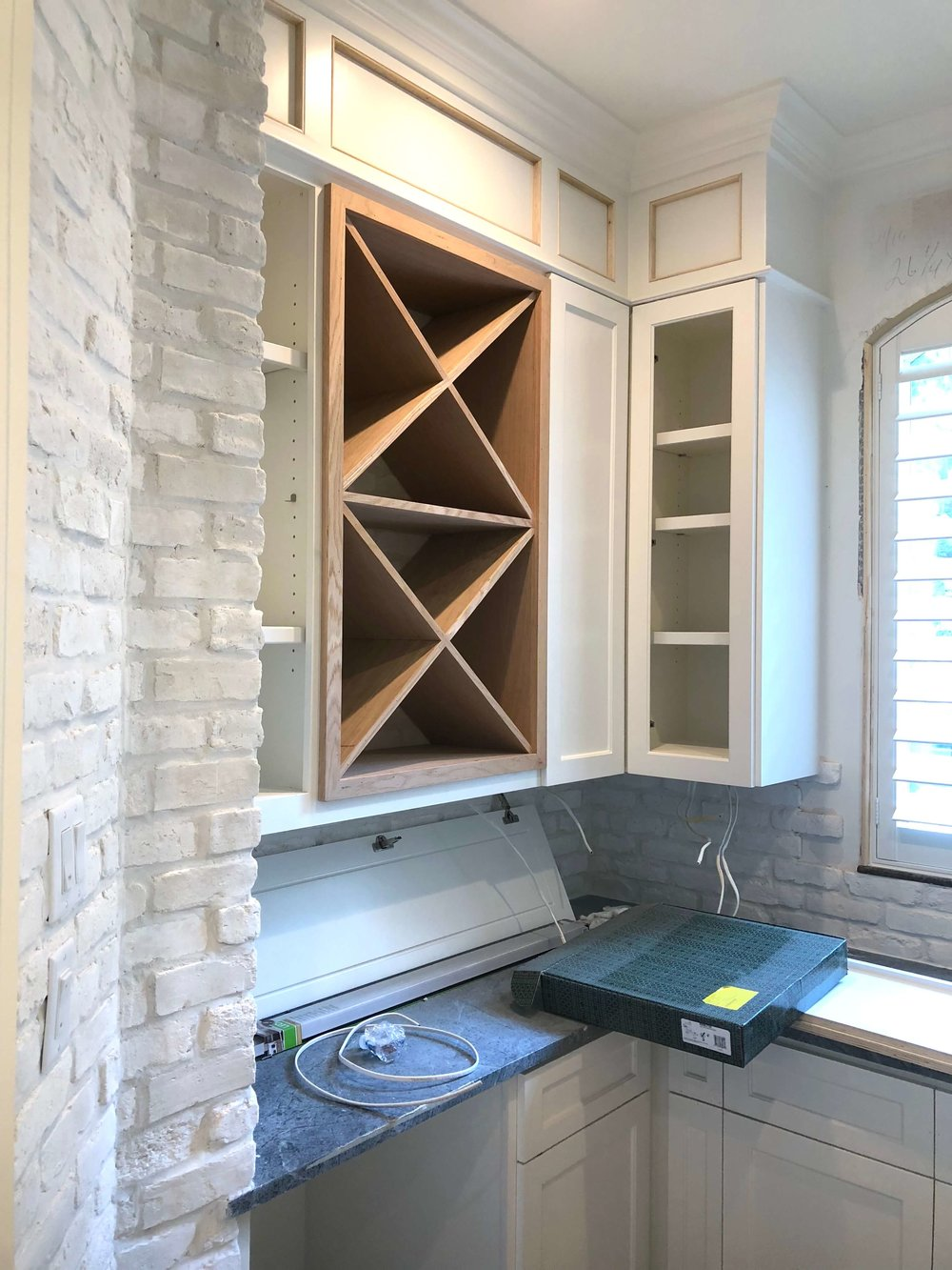 New built-in wine rack and cabinetry in Butler's pantry with brick walls and soapstone countertops