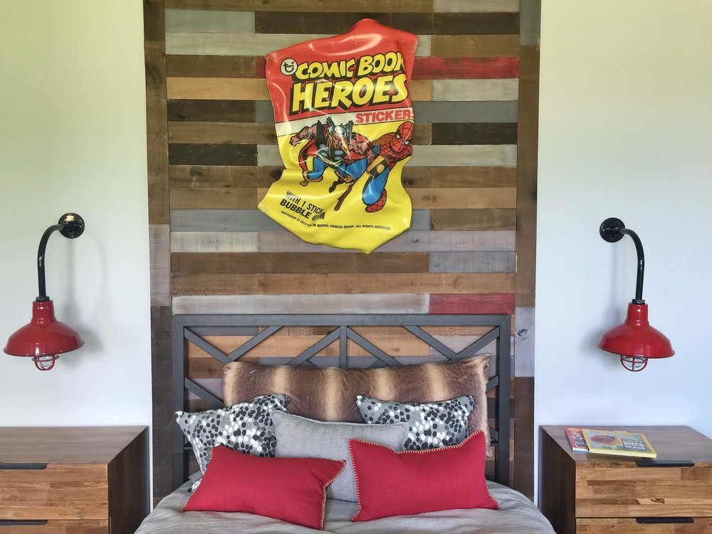Fun comic book art piece above the bed in boy's bedroom with shiplap walls and barn lights - Designer Shundra Harris