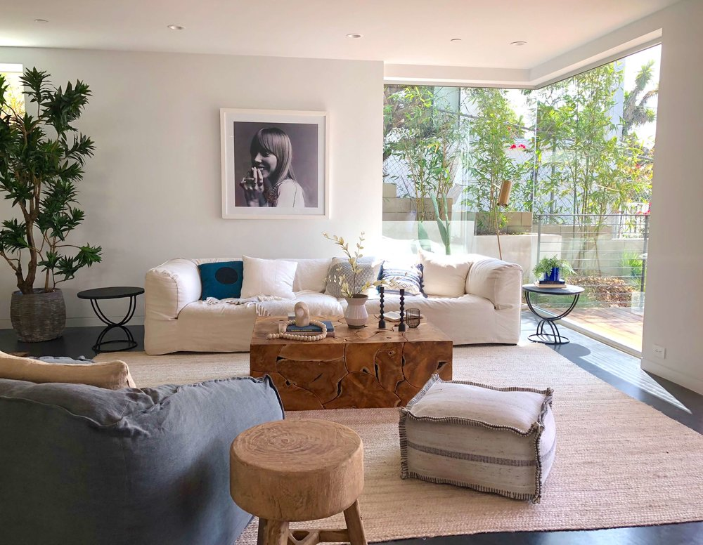Large corner windows in living room with extra long sofa - California Home Tour