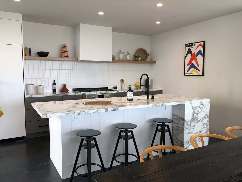 Kitchen with white marble, floating shelf, charcoal lower cabinets - California home tour