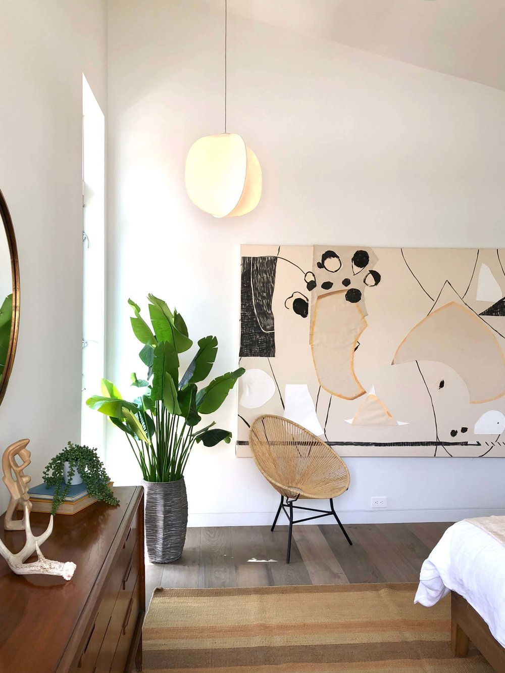 Large modern art in master bedroom with tall corner window | California home tour