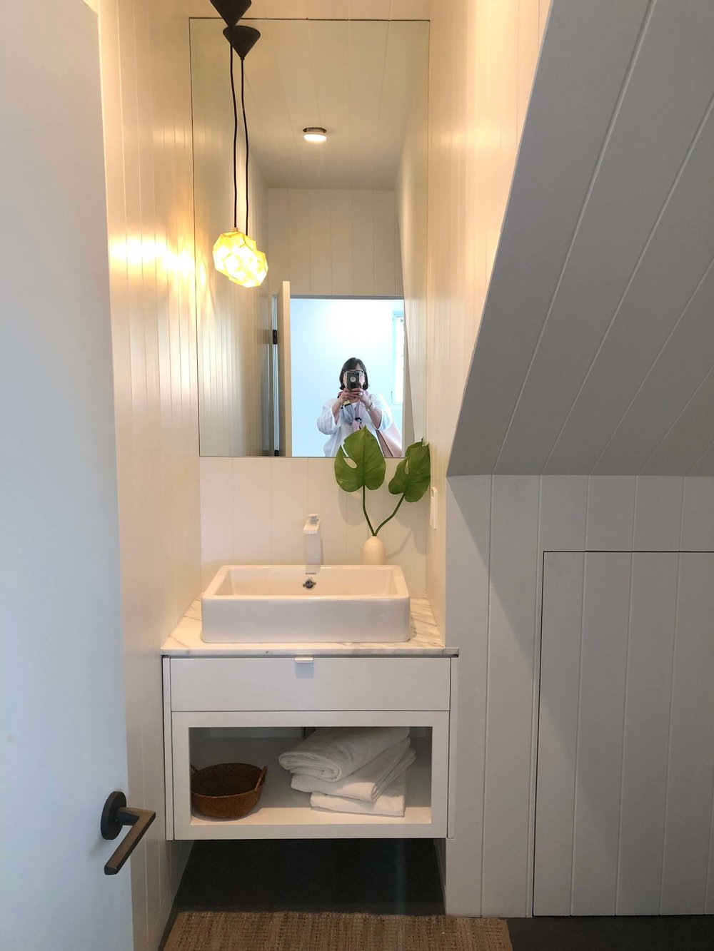 White powder room with side pendant light and vertical shiplap | California Home Tour