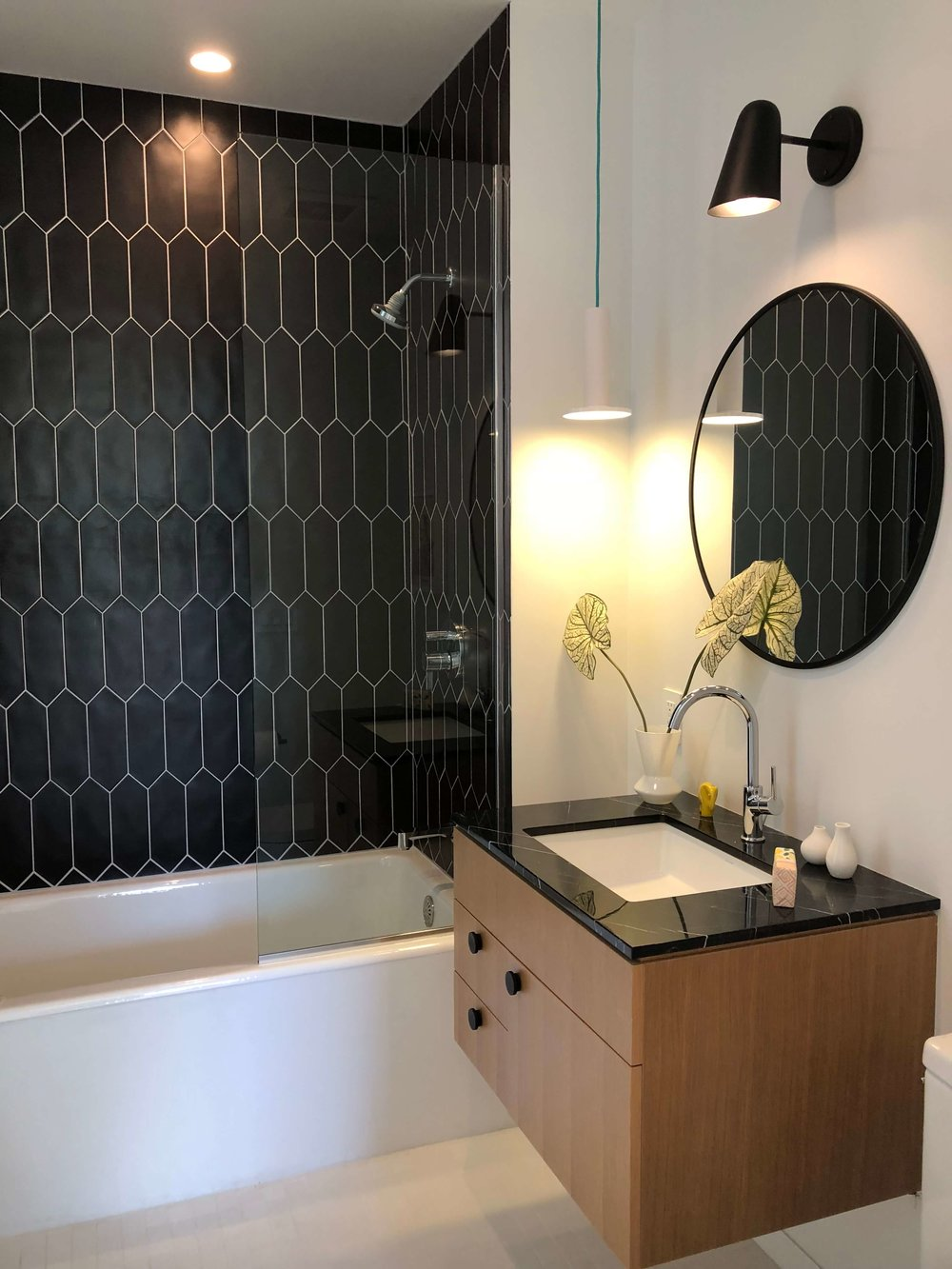 Black and white modern bathroom with floating vanity and round mirror | California home tour