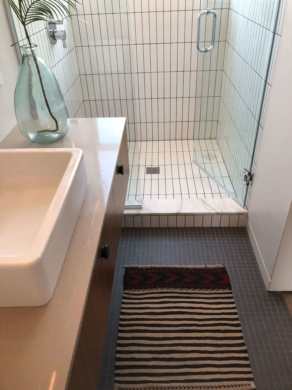 Modern bathroom with black mosaic tile floor and white tiled shower - California home tour