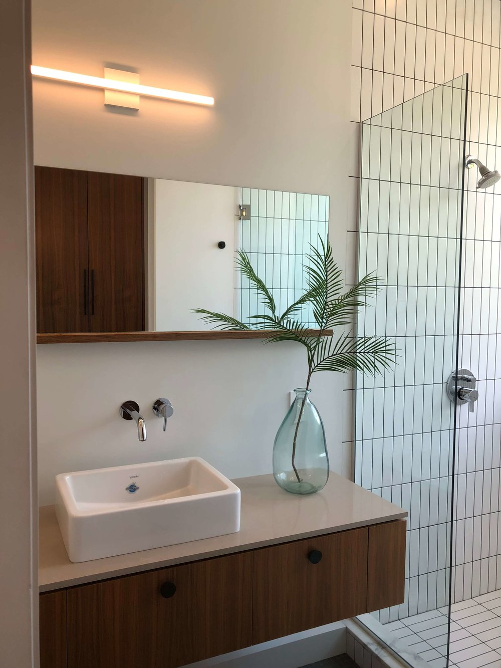 Modern bathroom with floating vanity, wall mount faucet, chunky vessel sink and LED vanity light - California home tour