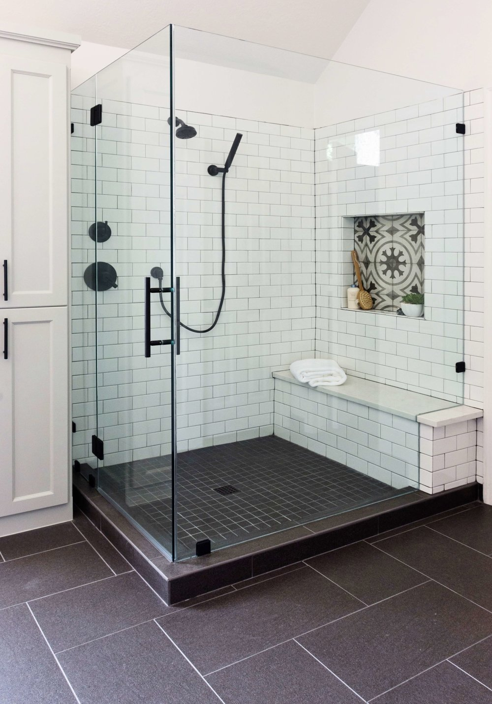 BEFORE AND AFTER - Master bathroom remodel, new shower with cement look tile shampoo niche, white subway tile with dark grout, bench and black plumbing fixtures  | Carla Aston, Designer | Charles Behrend, Photographer #cementtile #largeshower #subwaytile #bathroomremodel