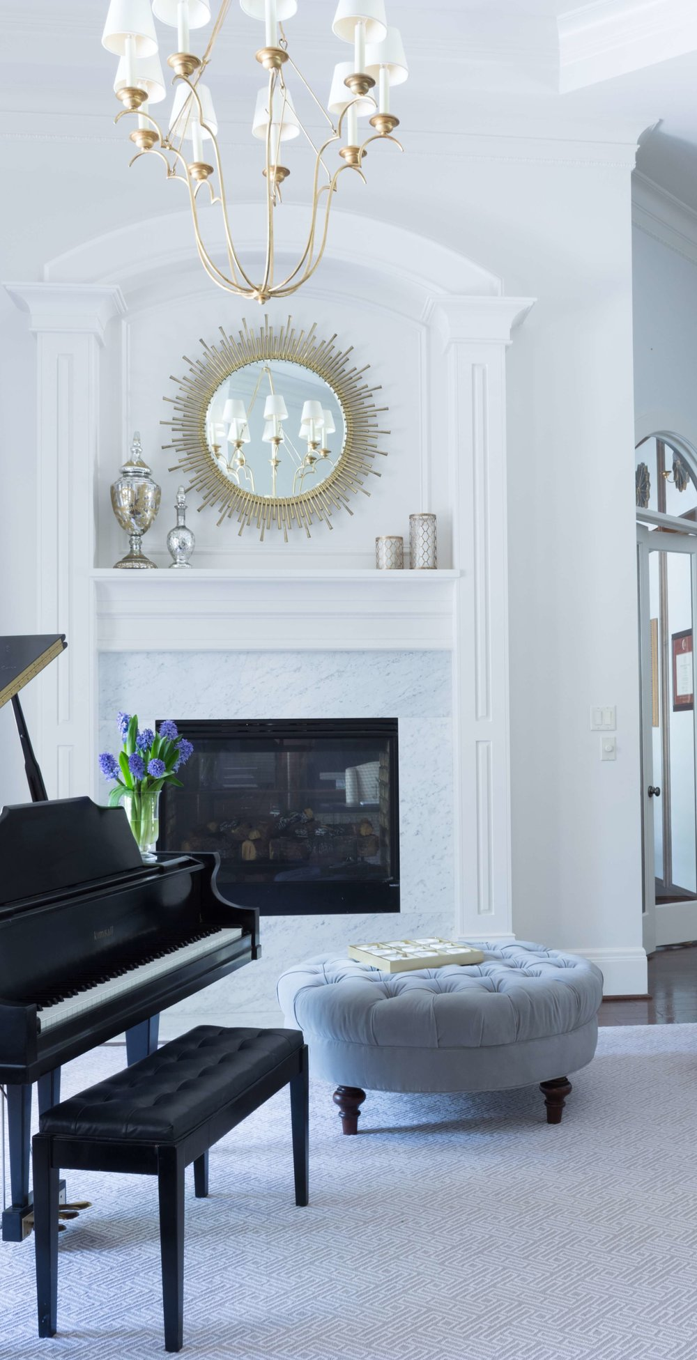 Making a formal living room a little more child-friendly | Formal living room with grand piano, white marble fireplace, gilded mirror and chandelier, Crypton velvet ottoman | Designer: Carla Aston