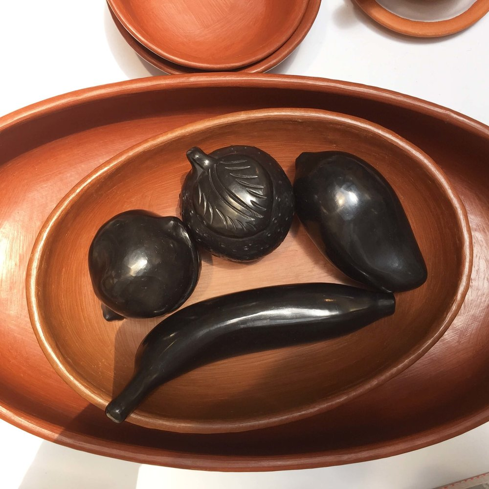 Handmade ceramics and black marble carved fruit seen a Dallas market from Mexico