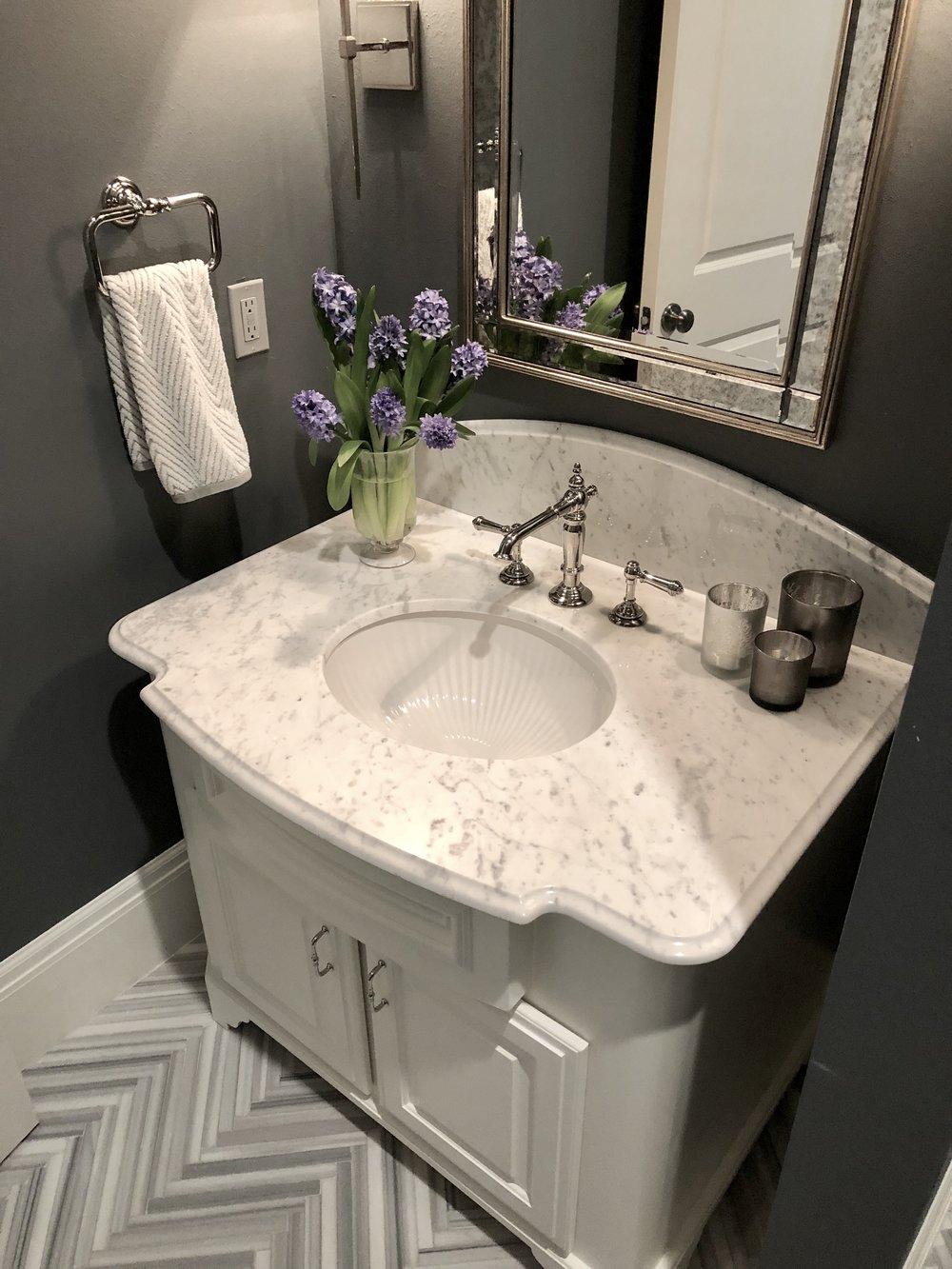 POWDER BATH ROUND UP |Gray powder bath with herringbone marble tile floor, Carrara marble countertop and curved splash | Designer: Carla Aston #powderbath #powderroom