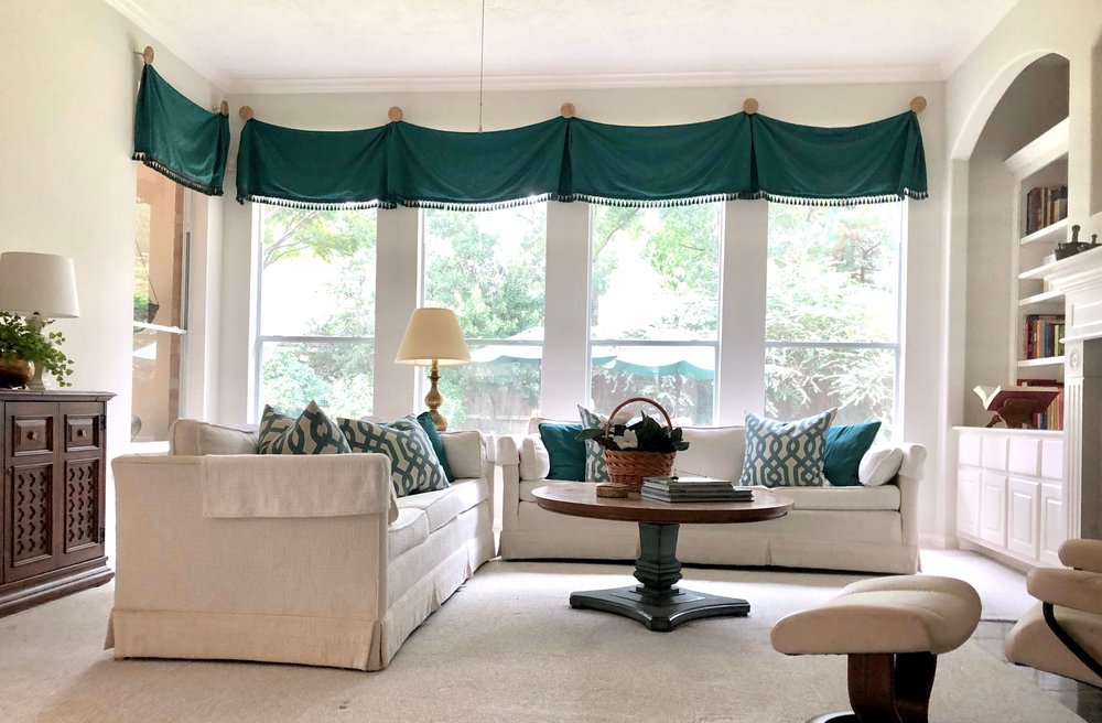 AFTER Staging - Here's the living room rearranged and staged with existing items ready for sale. The sheer curtains below the valance were removed for a better view to the garden and the furniture placement addressed to feel more open and inviting. Overall, we simplified the furnishings. #stagedtosell #homestaging #sellingahouse #stagingtosell #stagingideas