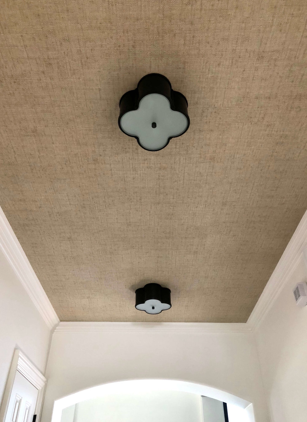 Grasscloth wallcovering on the ceiling makes for a textural, interesting backdrop to some sweet shapely ceiling mount light fixtures. #remodelingideas #ceilingdesign #lighting