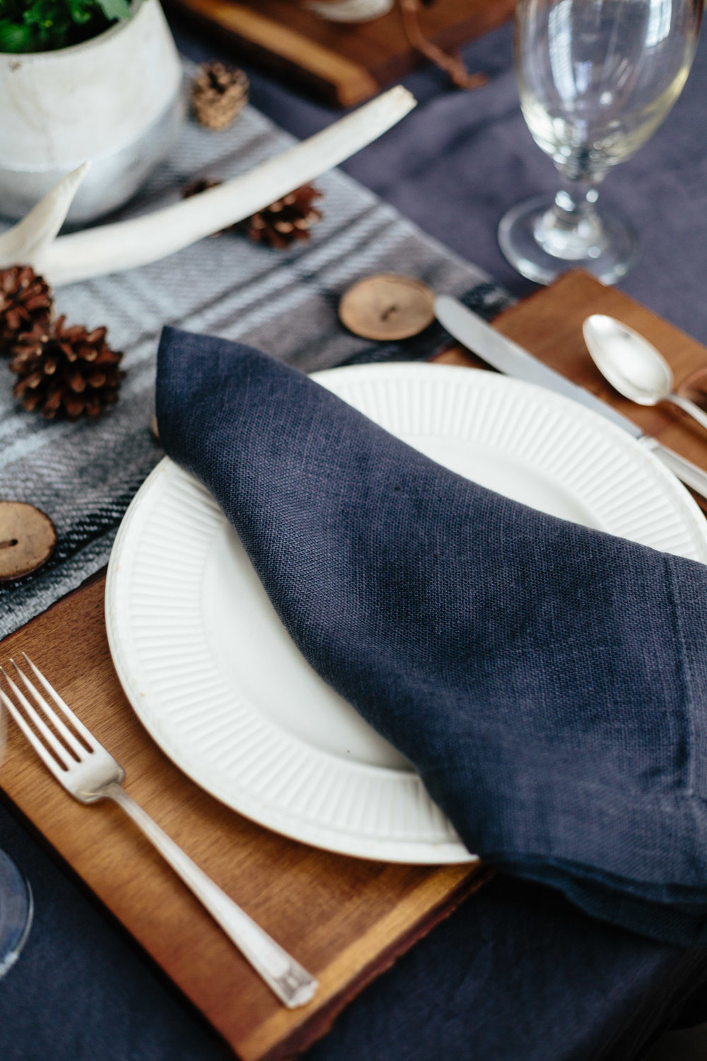Wood cutting board adds warmth to a gray tablesetting | Designer: Carla Aston, Photographer: Tori Aston #tablesetting #falltabletop #entertaining