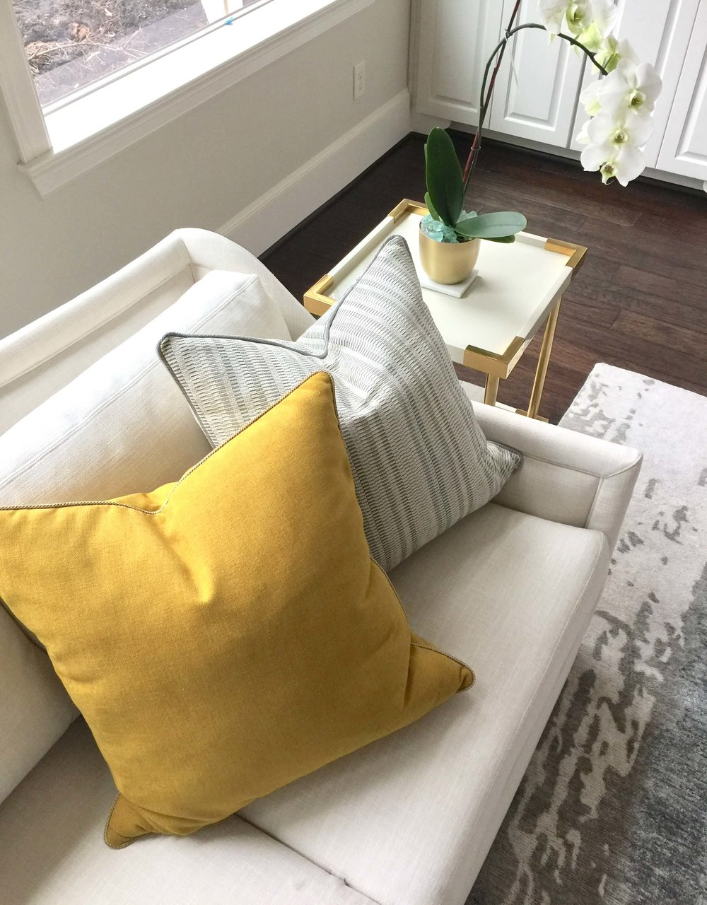 Yellow pillow with small pattern gray pillow on white sofa in living room | Designer: Carla Aston #pillows #throwpillows