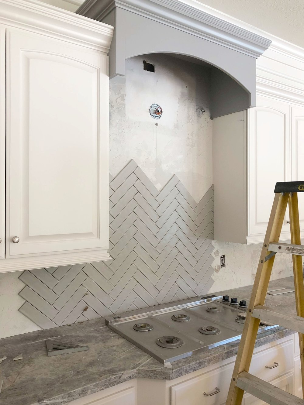 Gray herringbone tile backsplash going in now in kitchen remodel project | Designer: Carla Aston