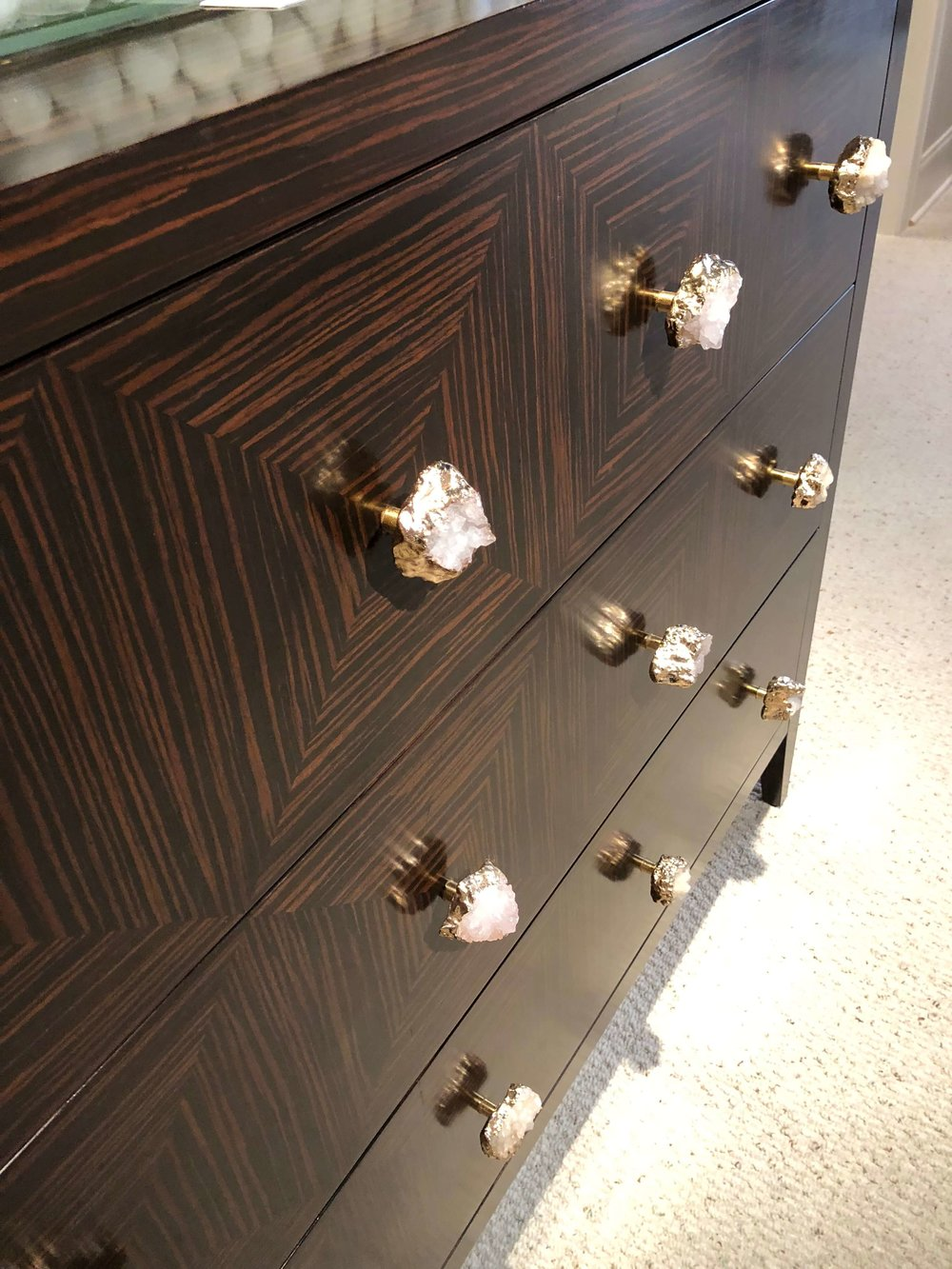 Dark wood console with quartz cabinet pulls - both brown wood and mineral trend all in one! From John-Richard.