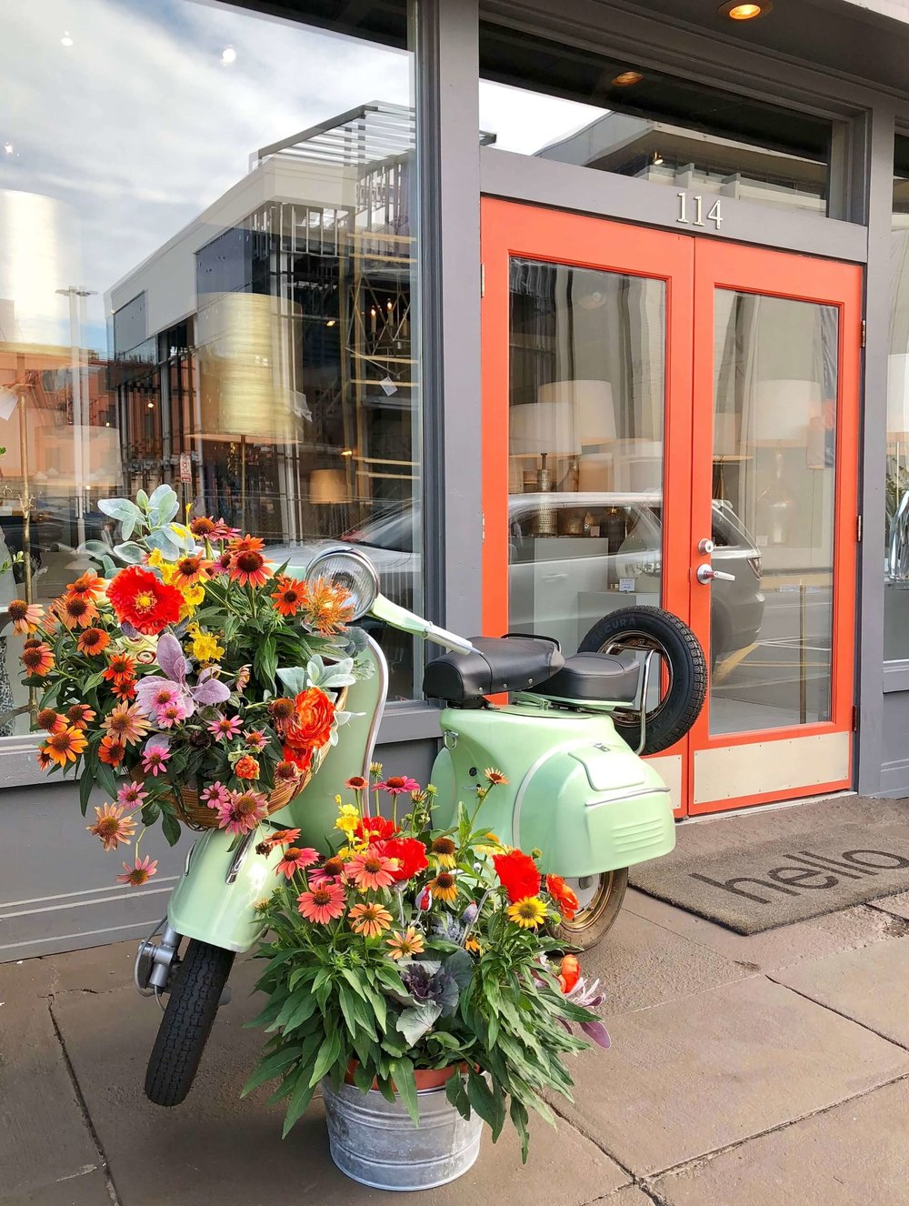 Floral display at the Mr. Brown showroom at Highpoint Market | #floraldisplay #freshflowers #scooter #frontdoor #curbappeal #holidaydecor #storefront