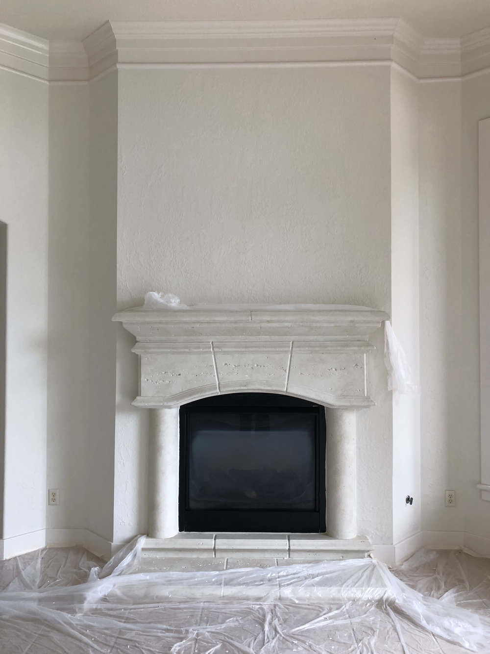 AFTER REMODEL - Living room fireplace with mouldings and walls matching in color for a spacious feel