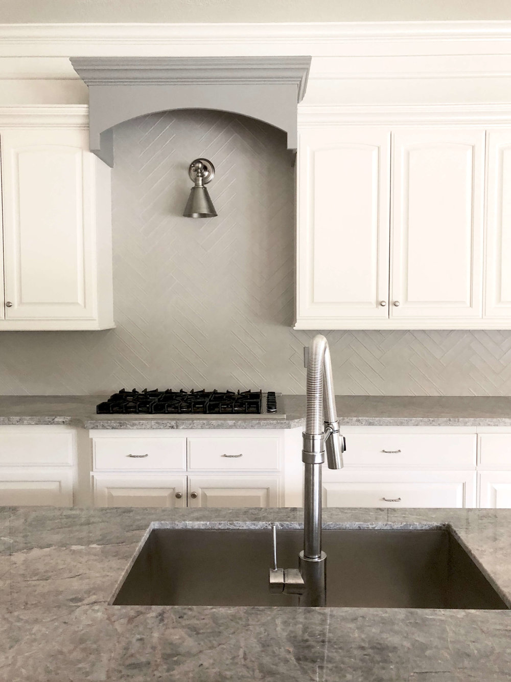 AFTER KITCHEN REMODEL - New countertops, backsplash, paint, cabinet pulls, lighting, sink, faucet | Carla Aston, Designer #remodelingideas #remodel #kitchenremodel #grayandwhitekitchen #herringbonebacksplash
