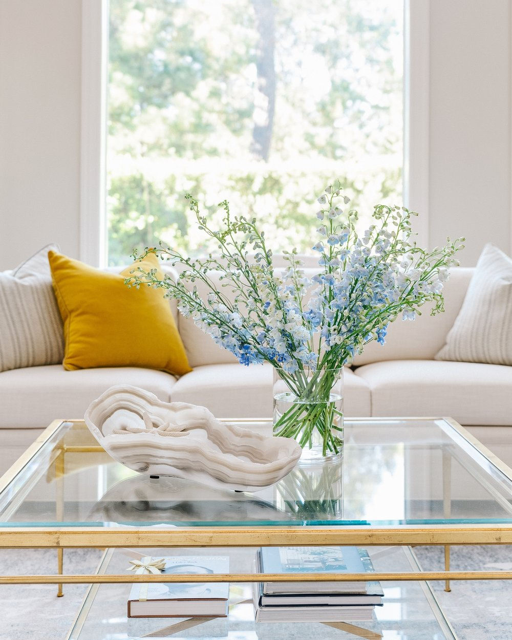 White sofa with gilded, glass top coffee table, yellow pillow, onyx bowl | Designer: Carla Aston, Contractor: Shaun Bain, Photographer: Colleen Scott #living room #livingroomideas #whitesofa #yellowpillow #coffeetable #coffeetablestyling