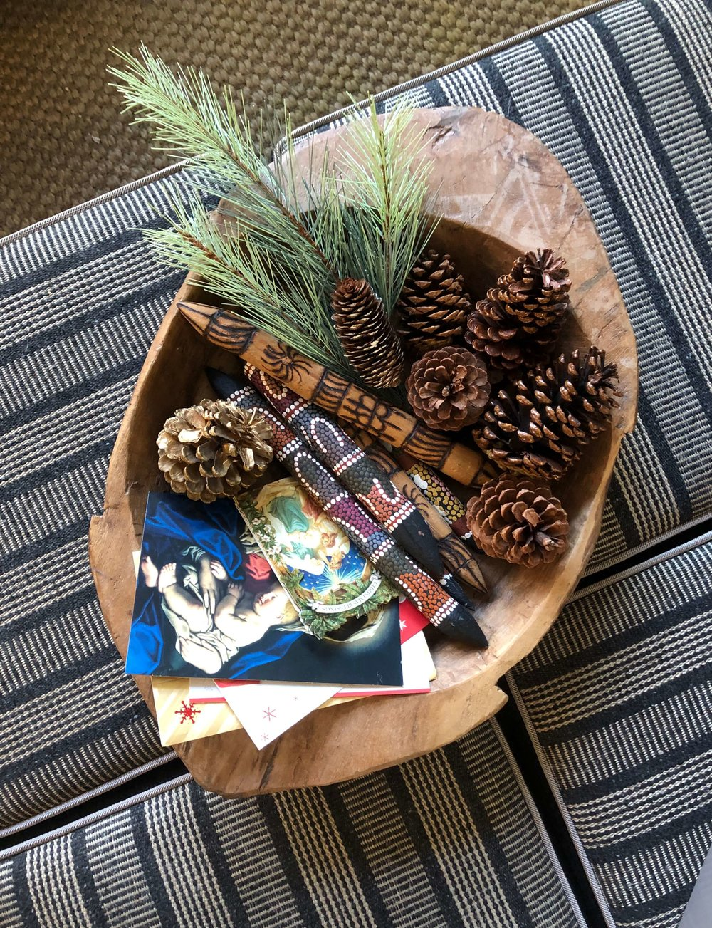 Christmas home tour - pinecones and cards in rustic wooden bowl on ottomans
