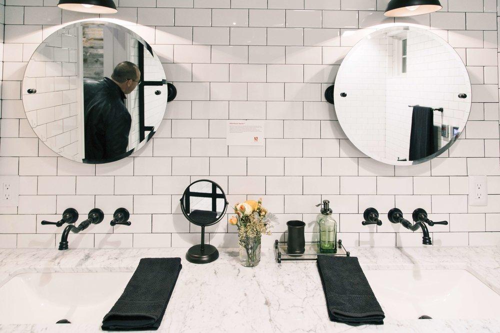 Black faucets in white tiled bathroom | Designer: Bobby Berk, Pardee Homes