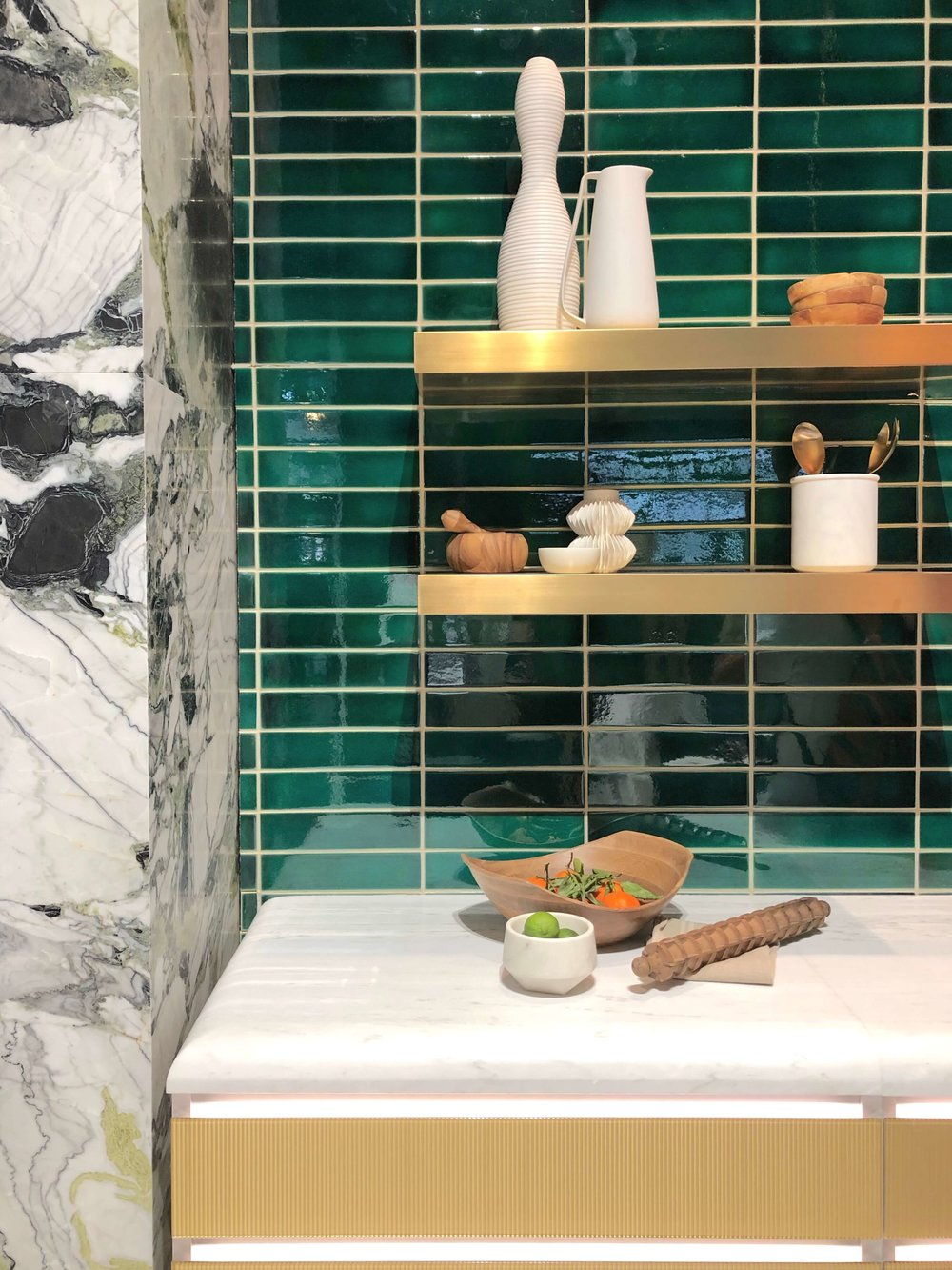 Hi-gloss linear subway tile in emerald green at Ann Sacks booth at KBIS 2019, shown with exotic marble, brass open floating shelves and white marble countertop