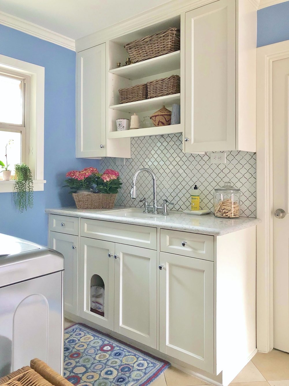 Pretty laundry room in periwinkle blue, cabinetry with deep utility sink and cubby for the cat box | Carla Aston, Designer