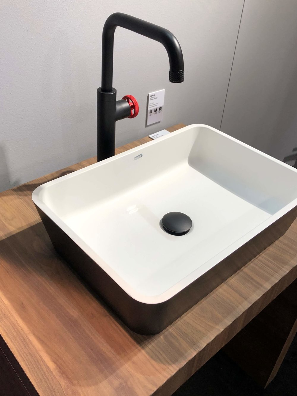 Black faucet with red handle and black and white metal vessel sink | KBIS 2019
