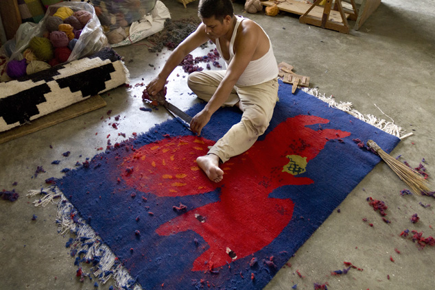 Artisans finishing a rug.