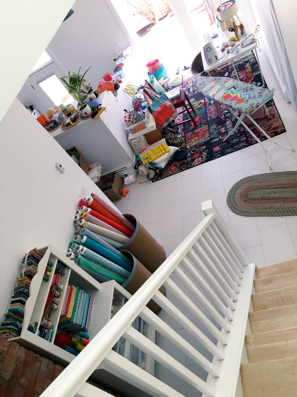 Here's an overview of the sewing area. It's at the base of the stairs and opens out to the deck. The neat areas are on the perimeter since I was taking pictures for the Look Book—everything else was piled up in the middle!