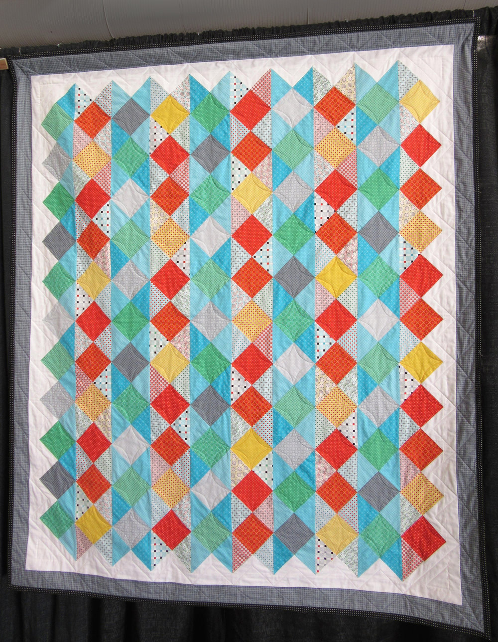 The pattern was designed by Nancy Mahoney and appeared in the Fons & Porter Scrap Quilts magazine, Spring 2015 edition. The fabrics are from  UPPERCASE Volume 2: Dots, Dashes and Diamonds , with the exception of the solid white.